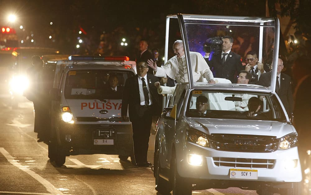 Pope Francis waves to Filipinos during his motorcade to the Apostolic Nunciature in Manila after his arrival in the Philippines.