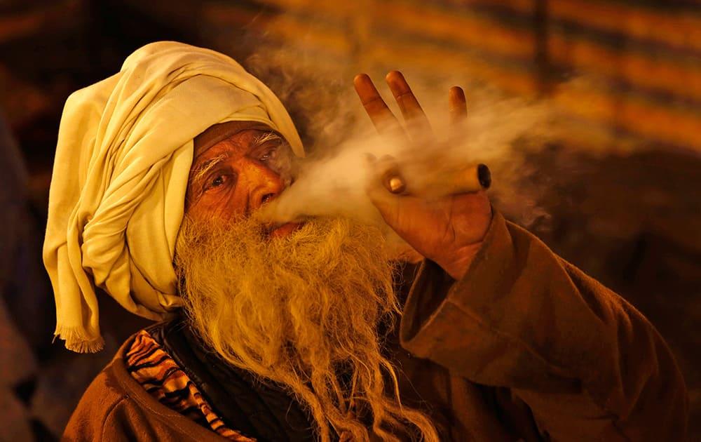A Sadhu or Hindu holy man smokes marijuana at