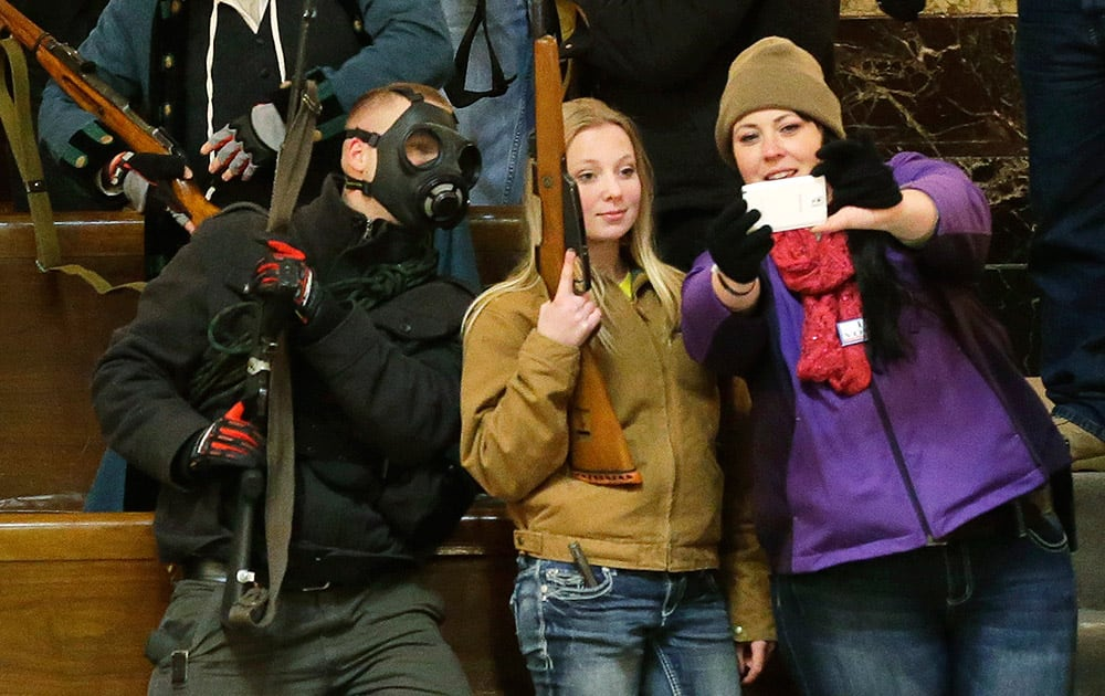Gun owners, including Garrett Bosworth, 16, center, of Yakima, Wash., pose for a selfie photo as they display their weapons in the upper gallery of the House chambers, at the Capitol in Olympia, Wash.