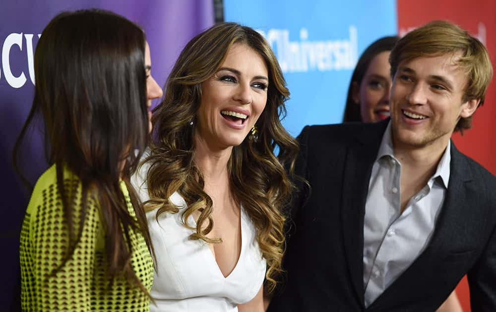 Elizabeth Hurley, a cast member in the E! series 'The Royals,' laughs with fellow cast members Alexandra Park and William Moseley at the NBCUniversal Cable 2015 Winter TCA Press Tour at The Langham Huntington Hotel, in Pasadena, Calif.