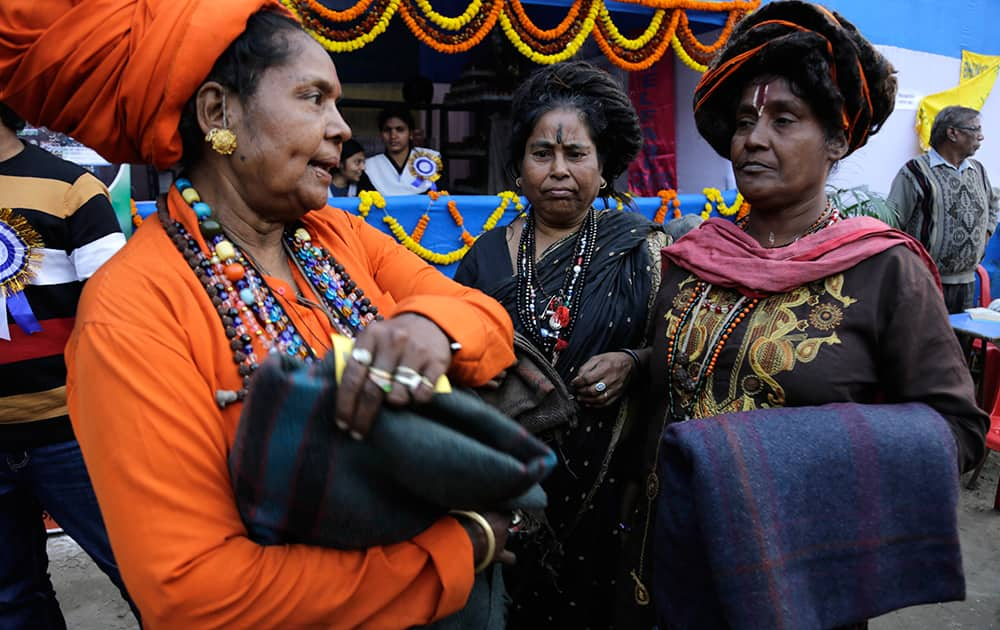 Hindu holy women talk after receiving blankets distributed by charitable trusts at a transit camp on the way to Gangasagar, in Kolkata.
