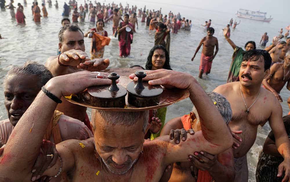 A Hindu devotee carries a pair of wooden slippers belonging to his late Guru, or spiritual teacher, on his head as a sign of respect after taking a holy dip to mark Makar Sankranti festival in Gangasagar.