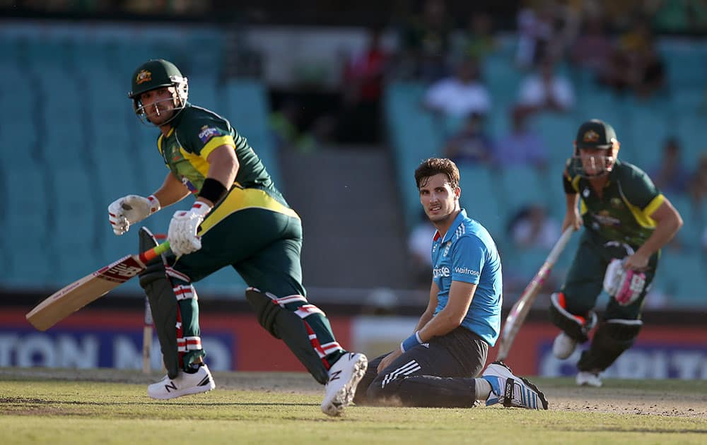 England's Steven Finn, center, watches from his knees as Australia's Aaron Finch, left, and David Warner make runs during their One Day International cricket match in Sydney.