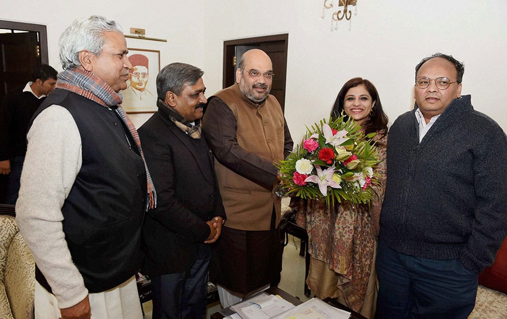 BJP president Amit Shah presents a bouquet to former AAP leader Shazia Ilmi at his residence, before she formally joins the party in New Delhi.