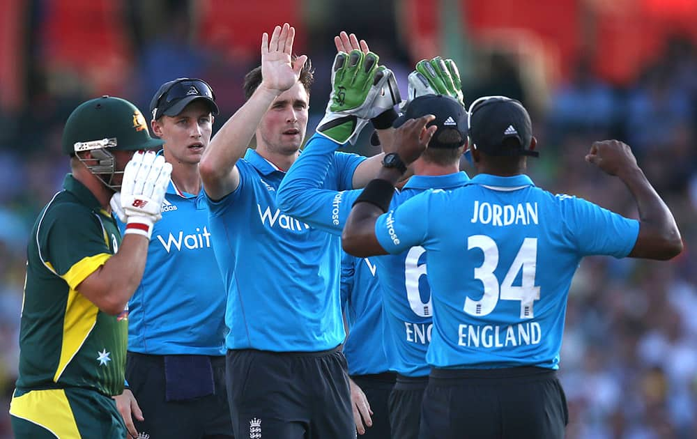 Englands Chris Woakes, celebrates with teammates after bowling out Australia's Arron Finch, for 15 runs during their One Day International cricket match in Sydney.