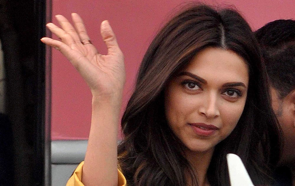 Deepika Padukone waves to her fans during shooting of her new film Tamasha in front of old Kolkata Airport terminal.