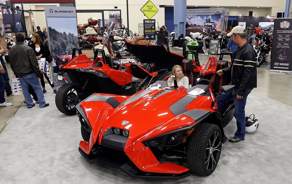Visitors check out a three wheel Polaris Slingshot, at a motorcycle show at the Miami Beach Convention Center in Miami Beach, Fla.