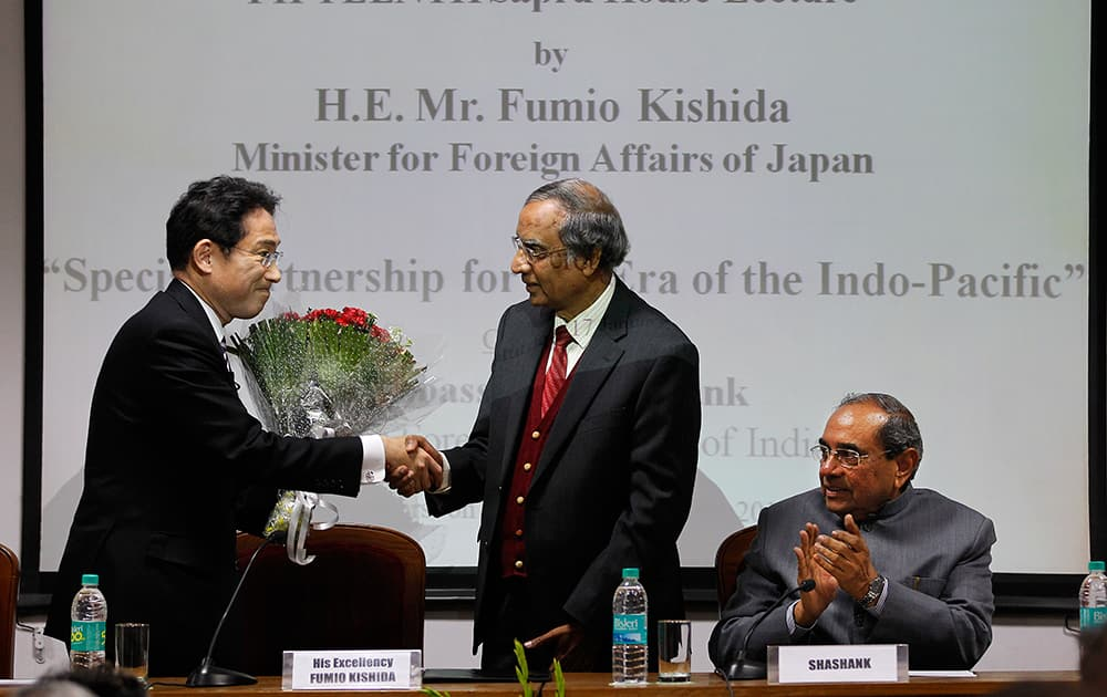 Japanese Foreign Minister Fumio Kishida, is greeted by Rajiv K. Bhatia, director general of Indian Council of World Affairs as former Foreign Secretary of India Shahank, applauds at the Indian Council of World Affairs in New Delhi, India.