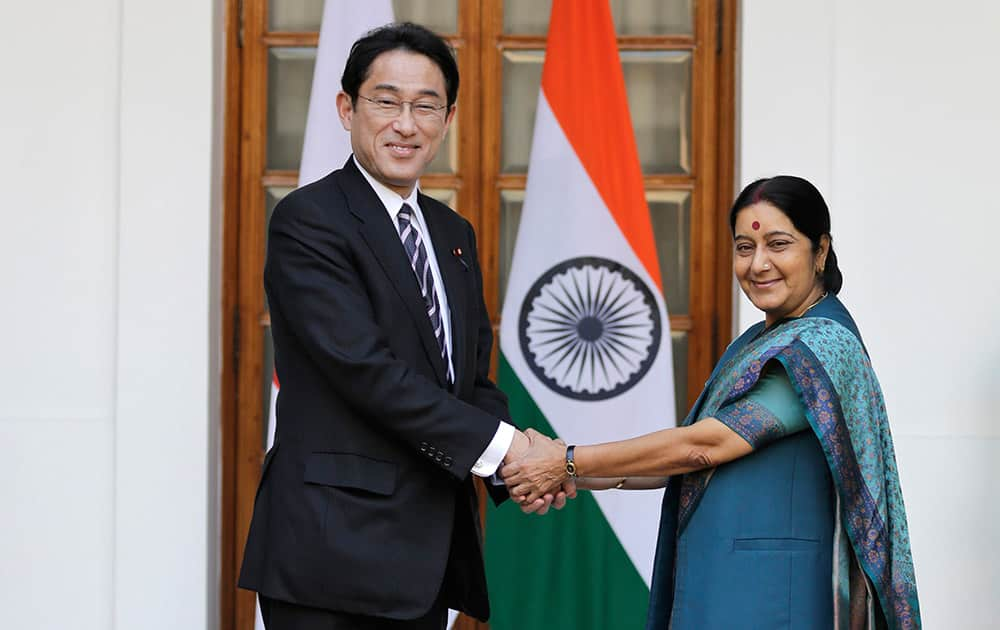 Japanese Foreign Minister Fumio Kishida shakes hand with Indian Foreign Minister Sushma Swaraj before the start of a meeting in New Delhi.