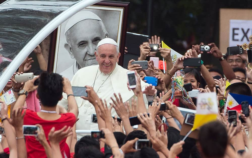 Pope Francis passes past a portrait of himself as he arrives to meet youths in Santo Tomas University in Manila, Philippines.