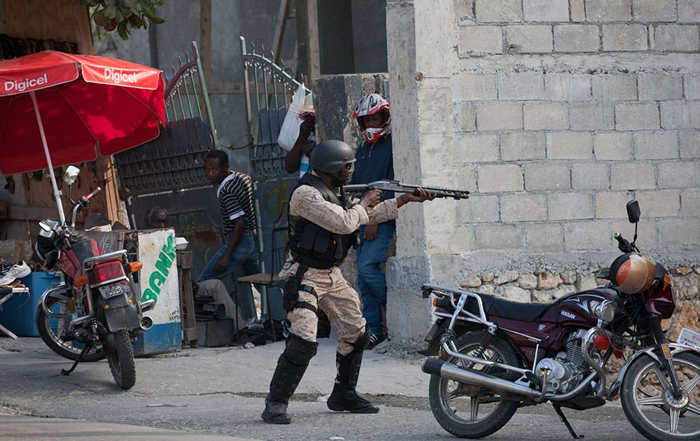 A National Police officer fires at protesters after clashes broke out with police during a demonstration to demand the resignation of President Michel Martelly, in Port-au-Prince, Haiti.