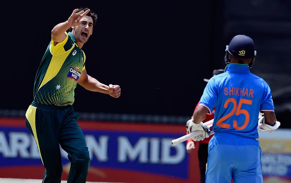 Australia's Mitchell Starc, celebrates the wicket of India's Shikhar Dhawan, right, during their one-day international cricket match in Melbourne.