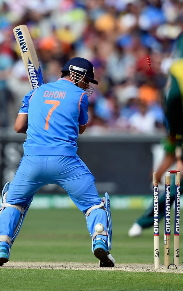 India's MS Dhoni looks at the stumps after being bowled by Australia's Mitchell Starc during their One Day International cricket match in Melbourne, Sunday.