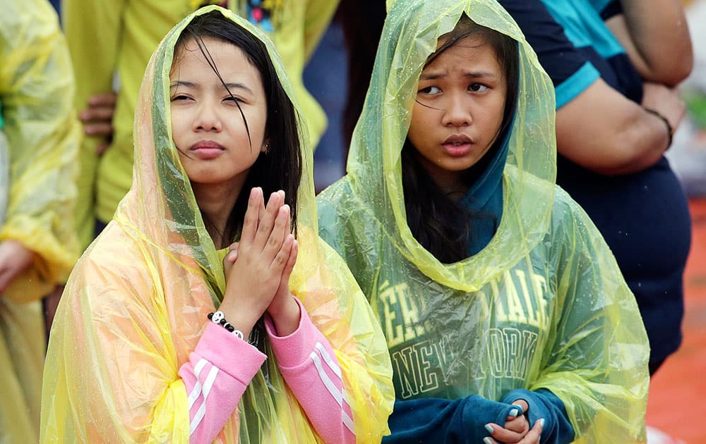 Young Filipino women pray during the visit of Pope Francis to meet the youth at the University of Santo Tomas in Manila, Philippines.