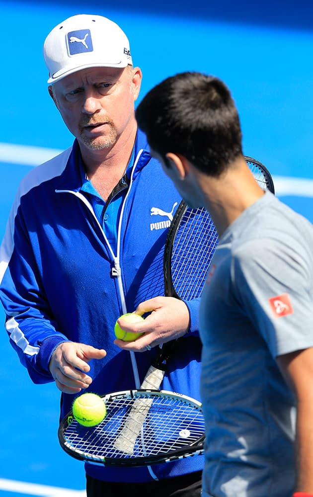 Boris Becker, coach of Novak Djokovic of Serbia, talks with Djokovic during a training session at the Australian Open tennis championship in Melbourne, Australia, Sunday.