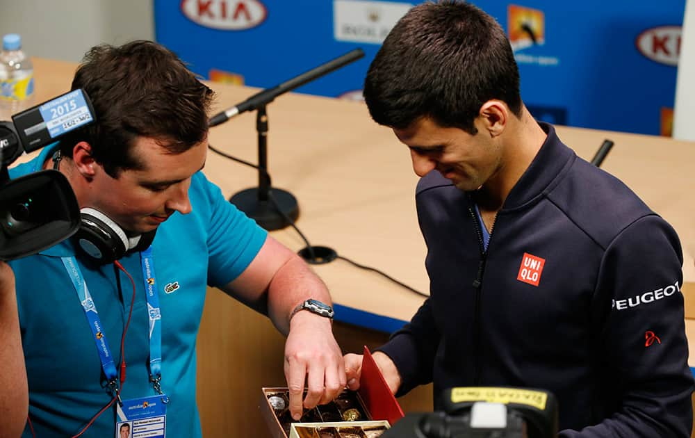 A reporter takes a chocolate from Novak Djokovic of Serbia, right, during a press conference at the Australian Open tennis championship in Melbourne, Australia, Sunday.