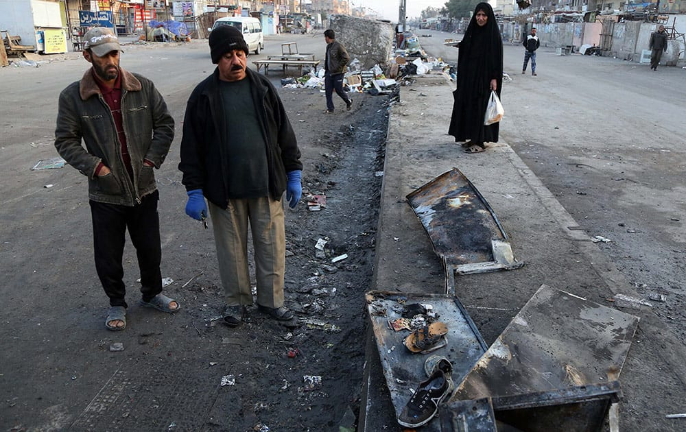 Iraqis inspect burned shoes that remain at the scene of a Saturday bomb explosion in Baghdad's Shiite district of Sadr City, Iraq, Sunday. A series of bombings targeting busy markets in and around the capital, Baghdad.