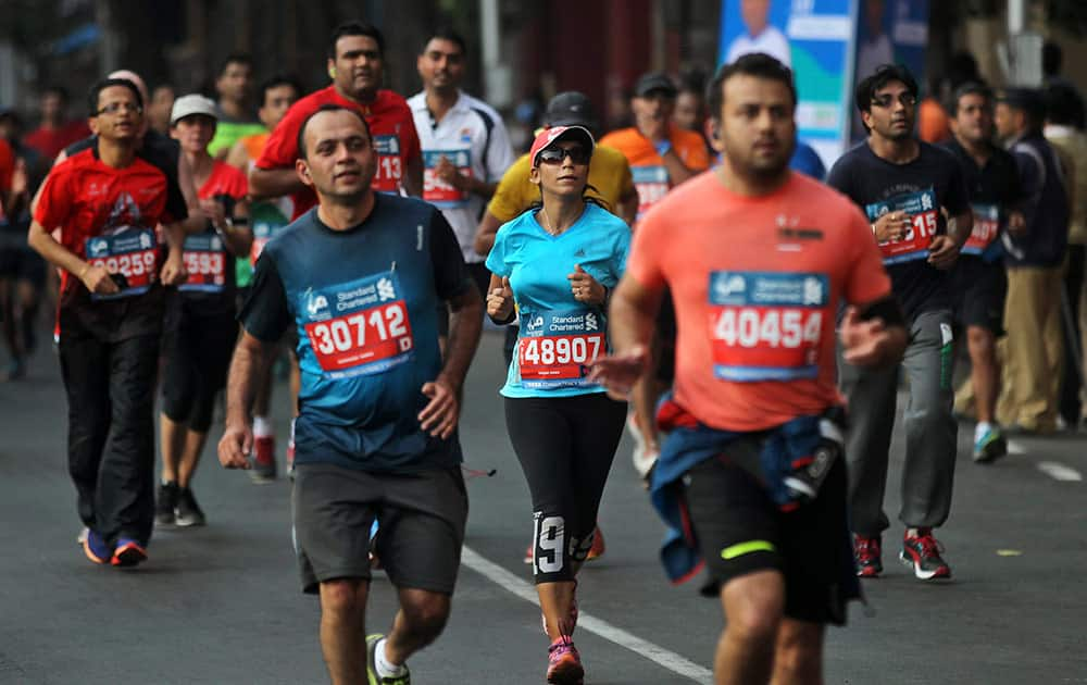 Competitors run during the Mumbai Marathon in Mumbai, India, Sunday. Thousands of city residents alongside athletes took part in the event.
