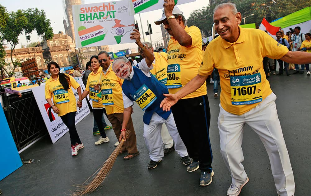 A participant, wearing a mask of India's Prime Minister Narendra Modi, holds a broom to join a countrywide campaign to clean parks, public building and streets, during the Mumbai Marathon in Mumbai.