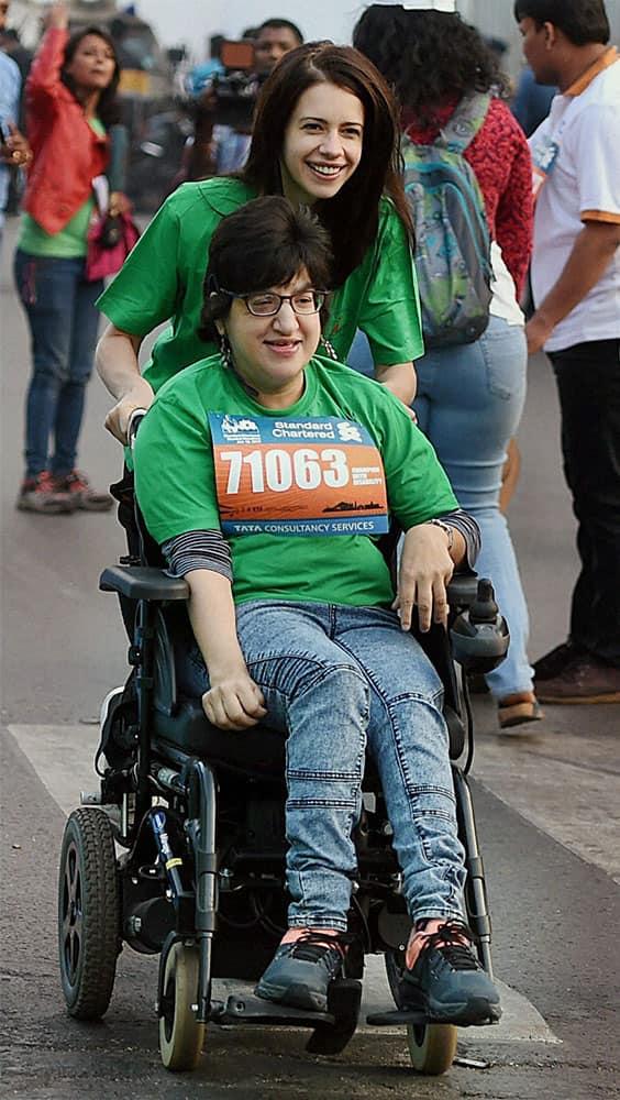 Bollywood actress Kalki Koechlin runs with a handicap girl during the Standard Chartered marathon.