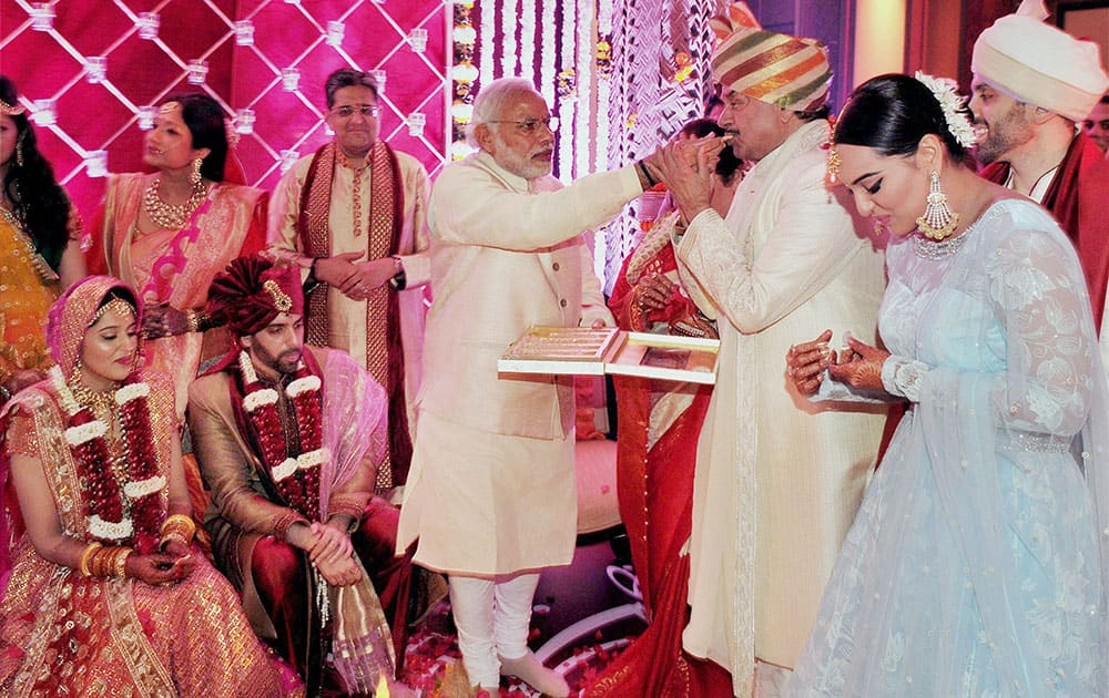 Prime Minister Narendra Modi gives a piece of sweet to Bharatiya Janata Party (BJP) MP Shatrughan Sinha on the occasion of his son, Kussh Sinhas wedding in Mumbai.