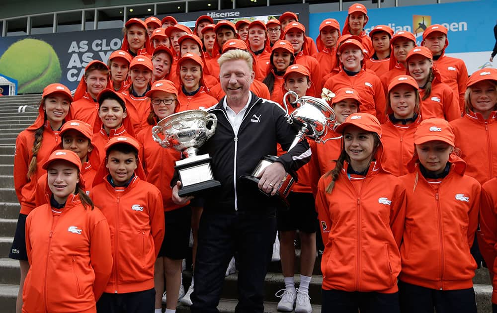 Former Australian Open champion Boris Becker holds the trophies of the men's singles and women's singles with ball kids, ahead of the first matches of this year's Australian Open tennis championship in Melbourne.
