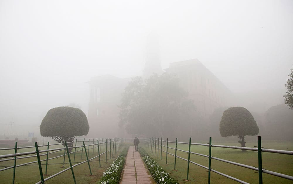 A person walks to his office amidst morning fog, in New Delhi, India.