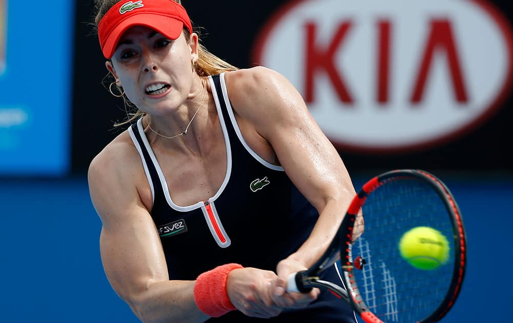 Alize Cornet of France makes a backhand return to Zhang Shuai of China during their first round match at the Australian Open tennis championship in Melbourne.