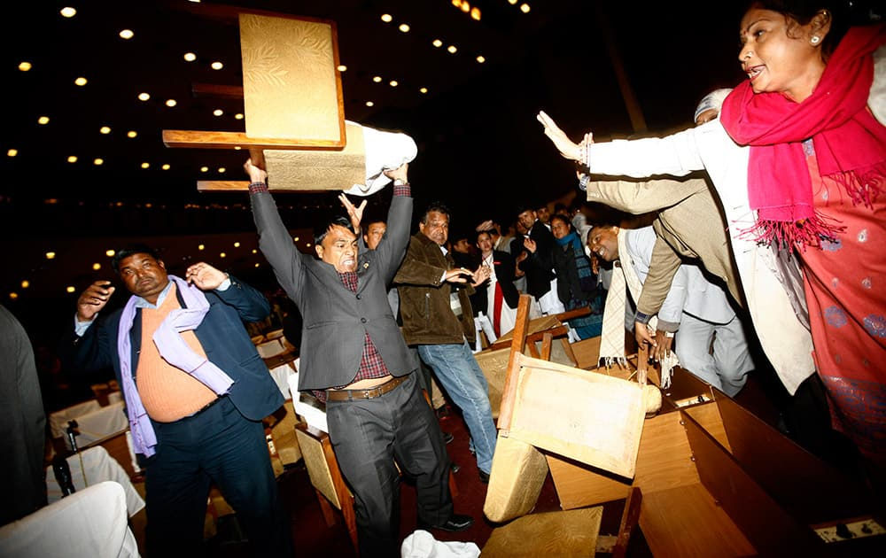 An unidentified Nepalese politician from the opposition party lifts a chair to throw, during the Constituent Assembly meeting, in Kathmandu, Nepal.