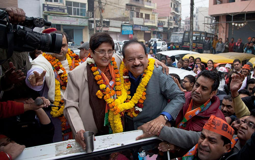 Bharatiya Janata Party chief ministerial candidate Kiran Bedi, left, and Union Health Minister Harsh Vardhan pose together during a road show before filing her nomination papers for the Delhi state elections in New Delhi.
