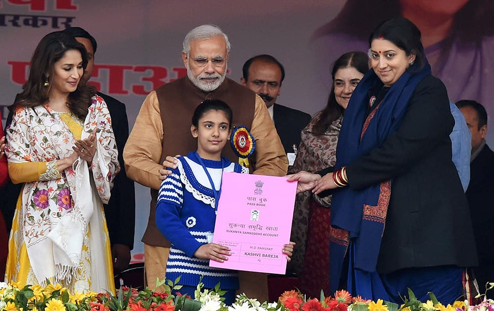 Prime Minister Narendra Modi with Union HRD Minister Smriti Irani presenting the Sukanya Samriddhi account pass-book to a girl during its launch at Beti Bachao Beti Padhao programme in Panipat.