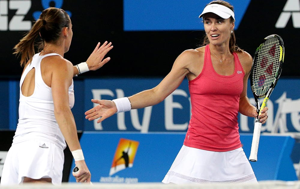 Martina Hingis of Switzerland and Flavia Pennetta of Italy touch hands as they play Daniela Hantuchova of Slovakia and Karin Knapp of Italy during their women's doubles second round match at the Australian Open tennis championship in Melbourne, Australia.