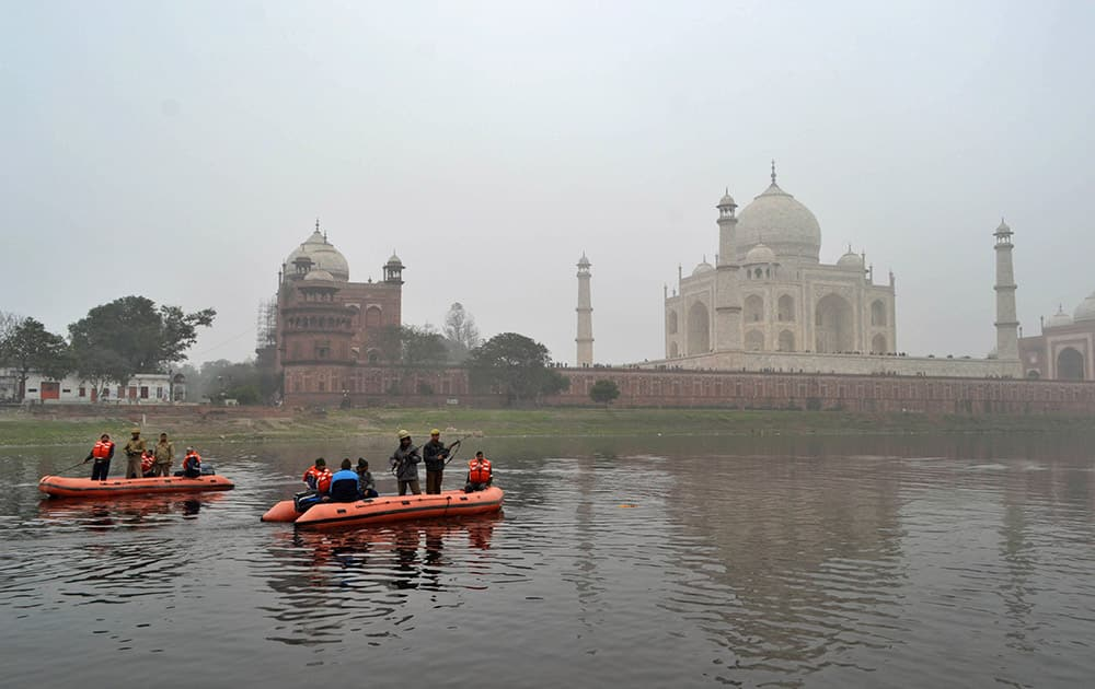 Policemen patrol through the Yamuna river passing the Taj Mahal monument in Agra.