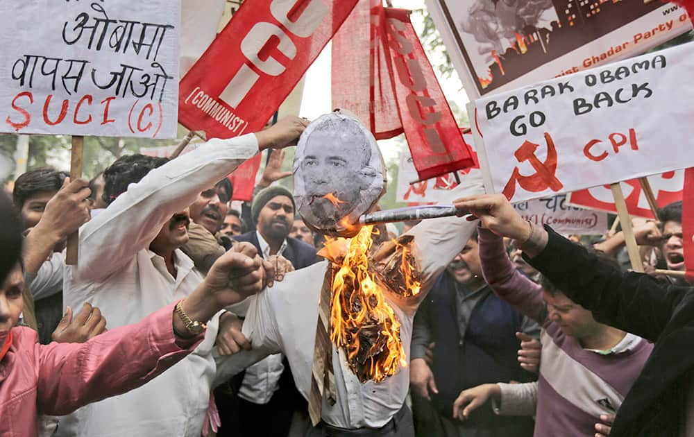 Members of various Left Front political parties set an effigy with an image of US President Barack Obama on fire during a protest march against his visit to India, in New Delhi.