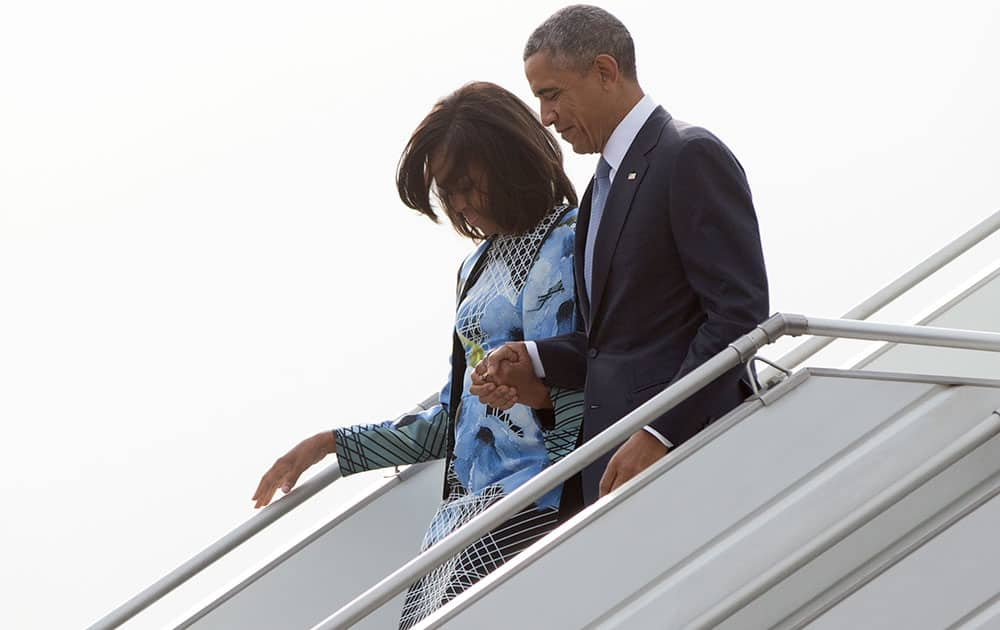 President Barack Obama and first lady Michelle Obama walk down the stairs as they arrive on Air Force One at Air Force Station Palam, in Palam, India.