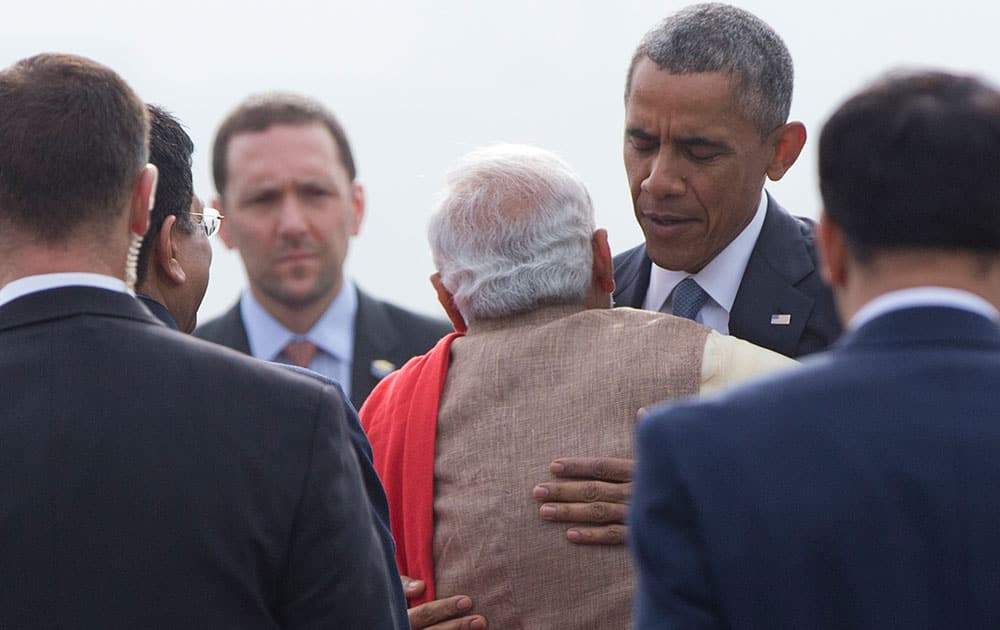 President Barack Obama embraces Indian Prime Minister Narendra Modi as he arrives with first lady Michelle Obama on Air Force One at Air Force Station Palam, in Palam, India.