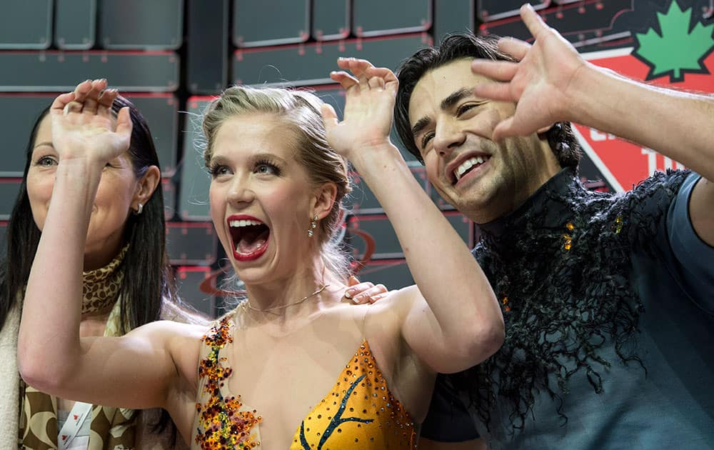 Kaitlyn Weaver and Andrew Poje react as their marks are posted for their free dance, to win the gold medal in the ice dance competition at the Canadian Figure Skating Championships.