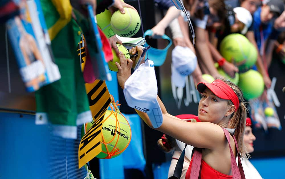 Maria Sharapova of Russia signs autographs for fans after defeating Peng Shuai of China in their fourth round match at the Australian Open tennis championship in Melbourne, Australia.