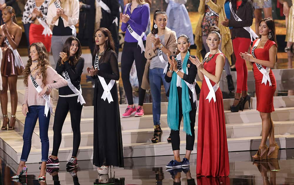 Miss Universe contestants clap as they rehearse, Saturday, Jan. 24, 2015, at Florida International University in Miami. The Miss Universe pageant will be held Jan. 25, in Miami.