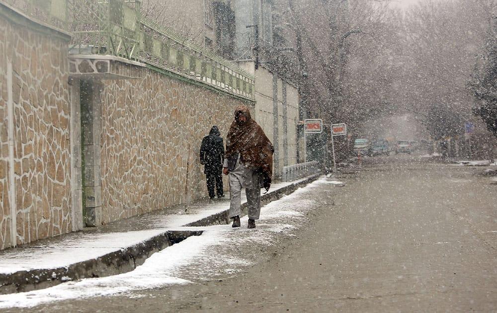 Afghan men walk during a snowfall in Kabul, Afghanistan.