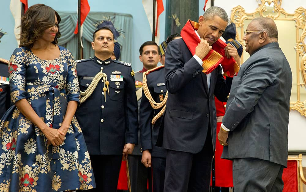 US President Barack Obama, second right, receives a scarf from a member of parliament who chairs the Committee on the Violation of Protocol Norms and Contemptuous Behavior of Government Officers, right, as first lady Michelle Obama stands left, during a receiving line before a State Dinner at the Rashtrapati Bhavan, the presidential palace, in New Delhi.