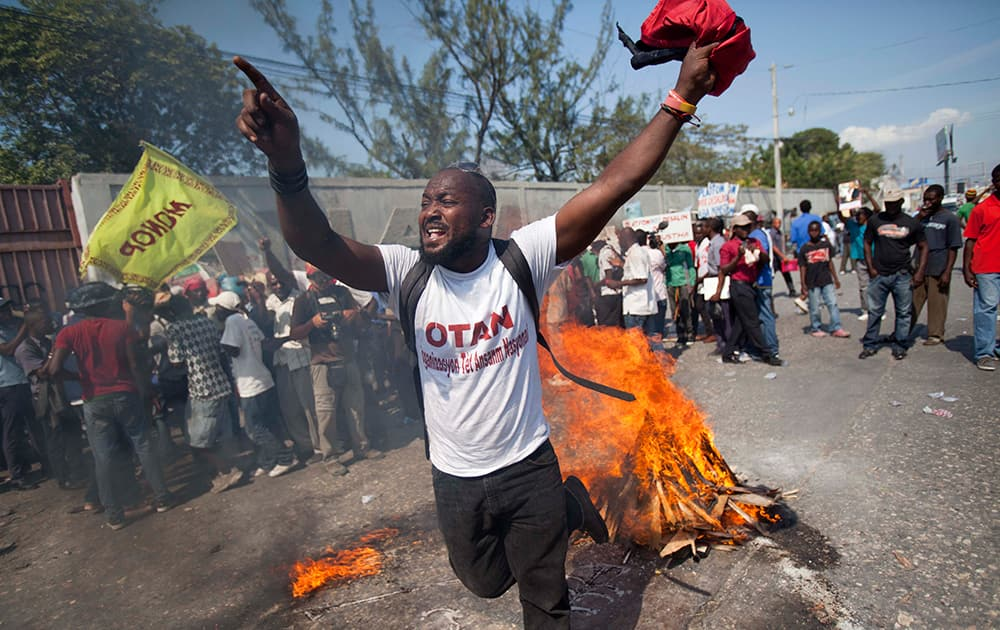A demonstrator uses wood, gas, fire and salt to call forth a spirit to ask for protection, in a voodoo ceremony before the start of a protest demanding the resignation of President Michel Martelly in Port-au-Prince, Haiti.