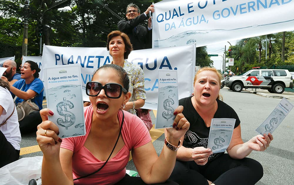 Demonstrators hold signs that reads in Portuguese