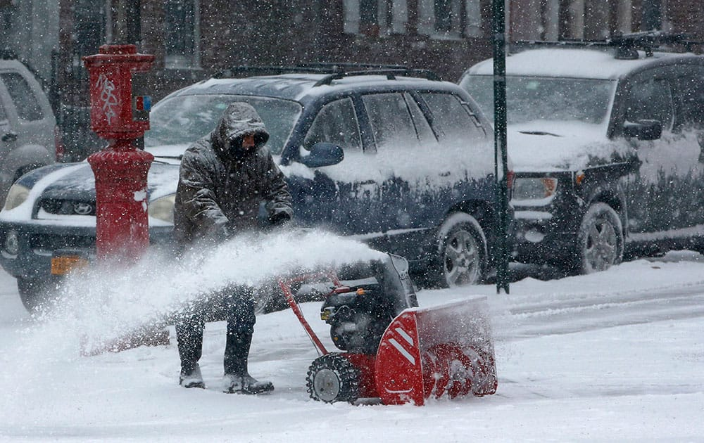 A man uses a snowblower to clear a path in the Windsor Terrace neighborhood, in the Brooklyn borough of New York.