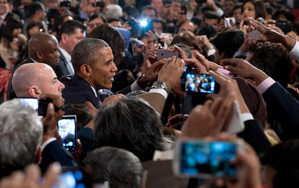 U.S. President Barack Obama greets people in the audience after speaking at the Siri Fort Auditorium in New Delhi.