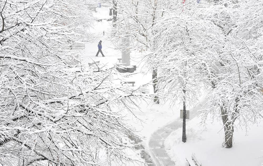 A pedestrian passes through Johnstown Central Park, in Johnstown, Pa. Gov. Tom Wolf declared a state of emergency Monday as a nor'easter expected to dump snow across the state approached.