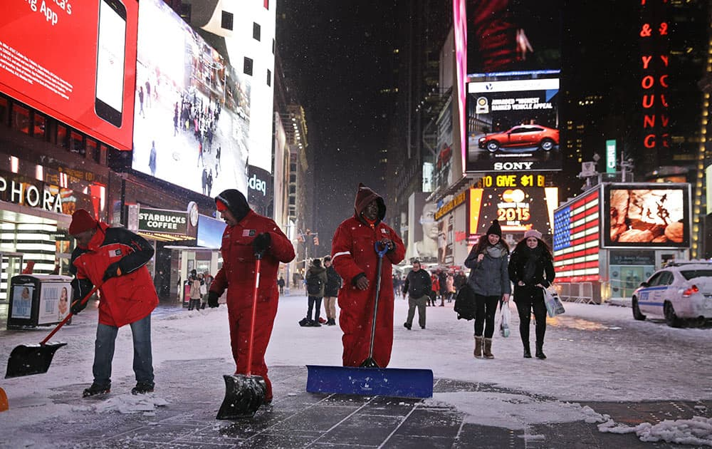 Men shovel a pedestrian walkway in New York's Times Square.