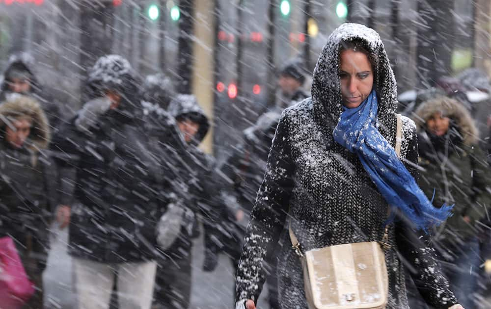 Pedestrians make their way through snow in New York. More than 35 million people along the Philadelphia-to-Boston corridor rushed to get home and settle in Monday as a fearsome storm swirled in with the potential of 1 to 3 feet of snow that could paralyze the Northeast for days.