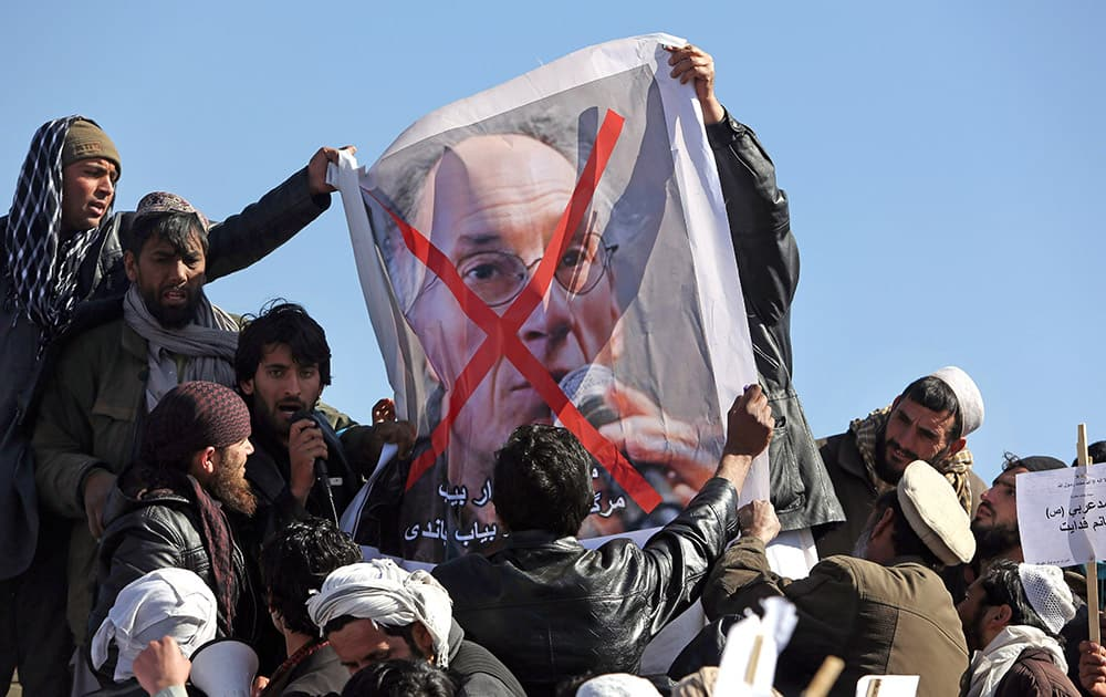 Afghans hold poster of French magazine Charlie Hebdo editor in chief, Gerard Briard, during a protest against caricatures published in the magazine in Kabul, Afghanistan.