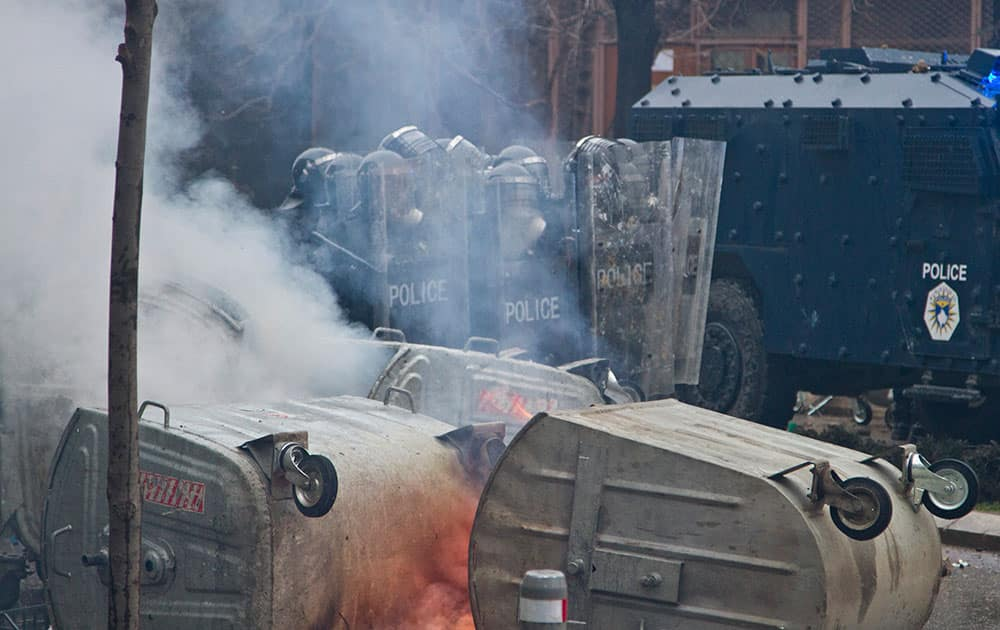 Police in riot gear are pelted with stones in Kosovo capital Pristina during a protest.